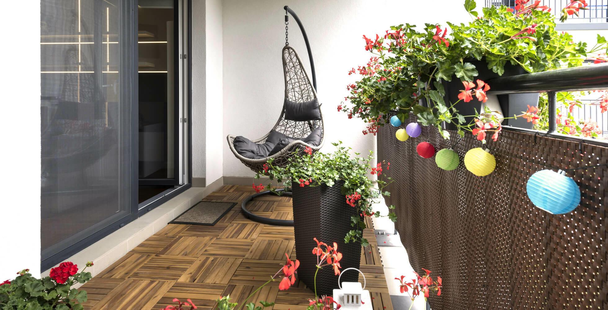 balcon décoré avec fauteuil suspendu et guirlandes style guinguette