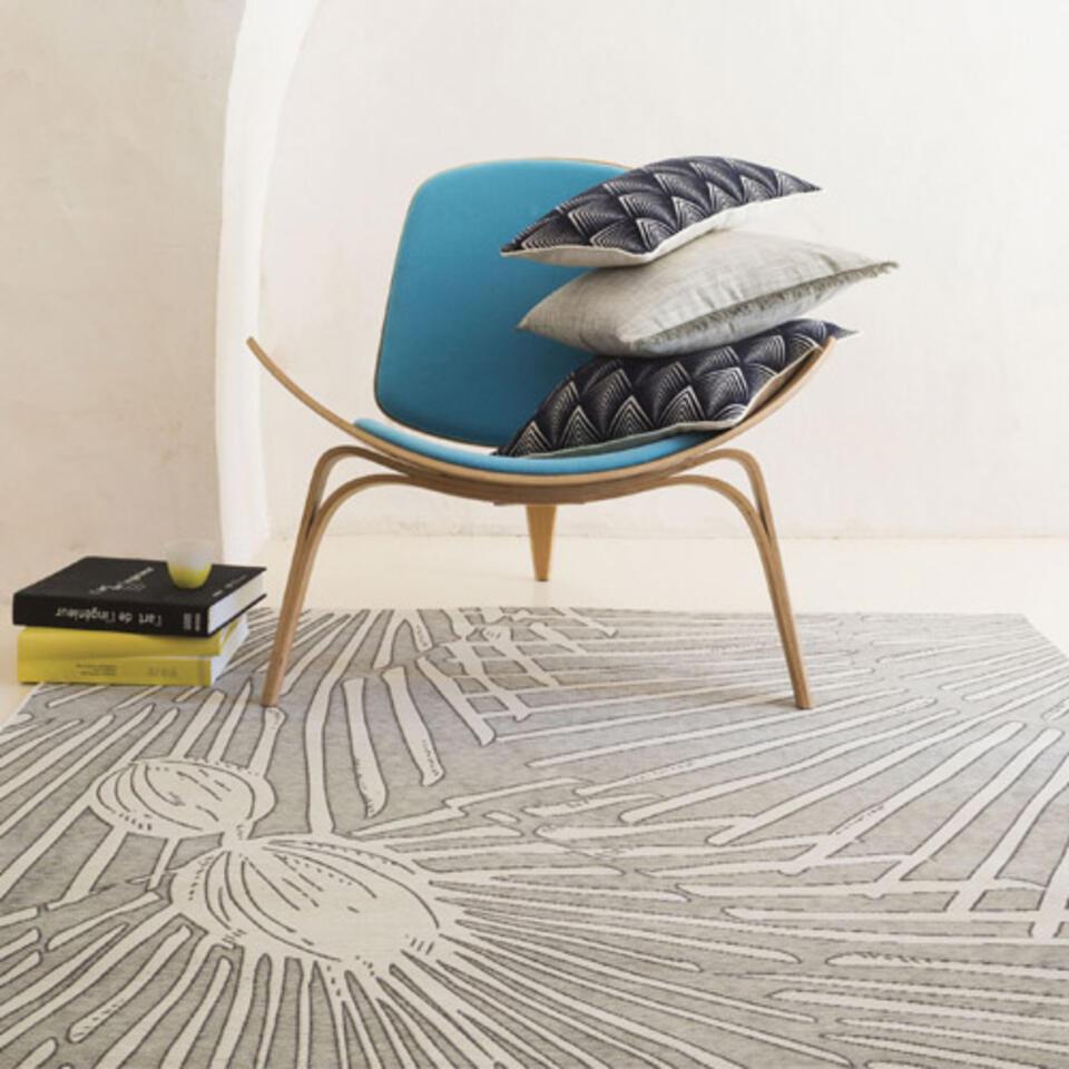tapis de salon gris à motifs placé sous un fauteuil