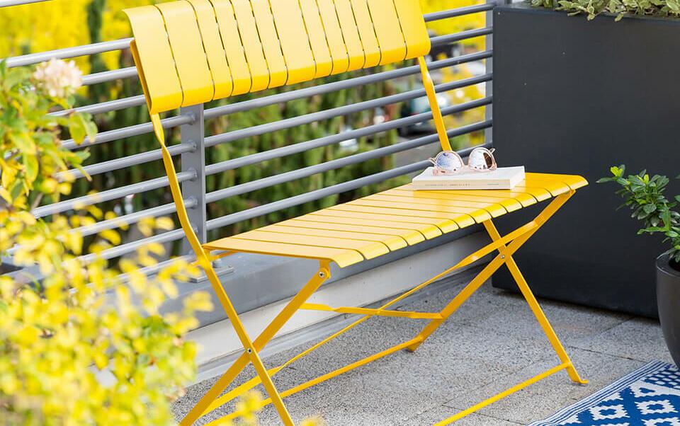 balcon avec petit banc jaune et arbres en pot