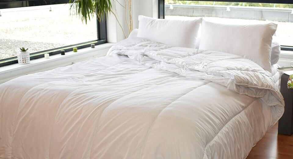 couette et oreillers blanc sur un lit